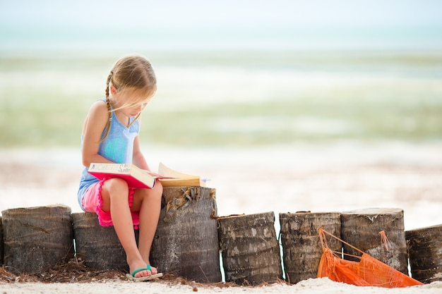 Piccolo libro di lettura adorabile della ragazza durante la spiaggia bianca tropicale