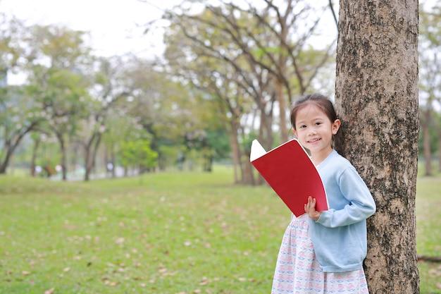 Piccolo libro di lettura asiatico della ragazza del bambino del ritratto nel magro diritto all'aperto del parco contro il tronco di albero con lo sguardo della macchina fotografica.