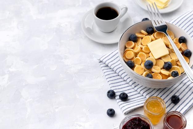 Piccolo mini pancake ai cereali. colazione fatta in casa con mirtilli, marmellata e caffè su sfondo grigio