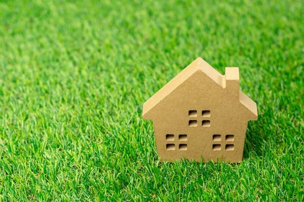 Piccolo modello di casa sul prato di erba verde.