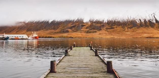 Piccolo molo in legno centrato su un lago, di fronte a una montagna innevata.