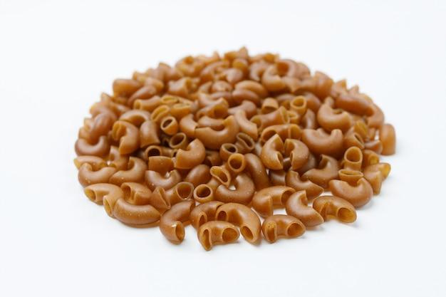 Piccolo mucchio di pasta di farina di grano saraceno su uno sfondo bianco
