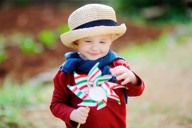 Piccolo mulino a vento sveglio del giocattolo della tenuta del bambino. ragazzo felice del bambino che tiene bandiera italiana all'aperto