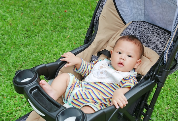 Piccolo neonato asiatico che si siede nel passeggiatore nel giardino verde.