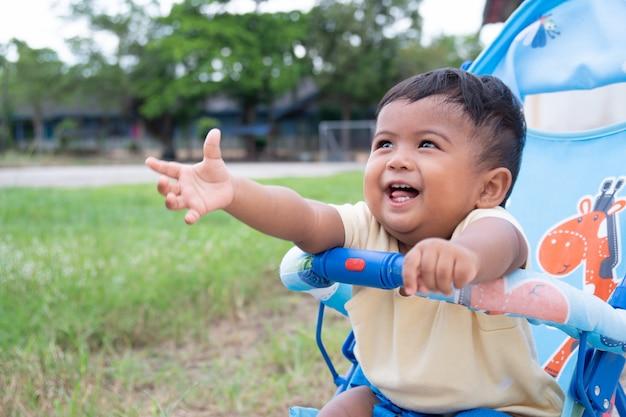 Piccolo neonato asiatico sveglio che si siede sul passeggiatore