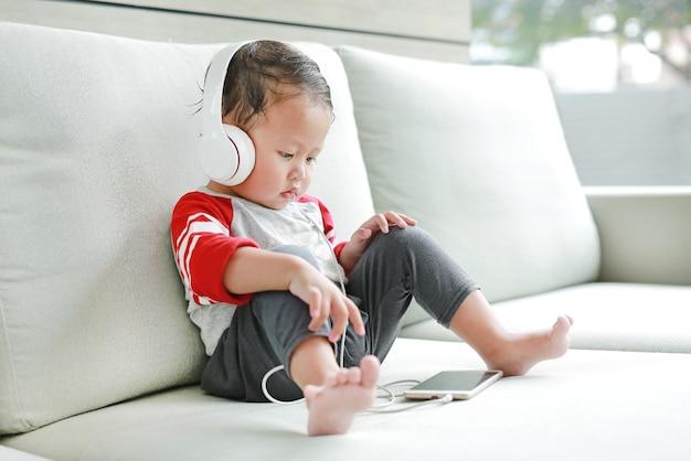 Piccolo neonato asiatico sveglio che si siede sul sofà e che ascolta la musica alle cuffie mentre esaminando telefono.