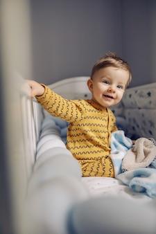 Piccolo neonato biondo allegro sveglio che si siede nella sua culla al mattino ed è felice di vedere i suoi genitori. sta anche aspettando la sua gustosa colazione.