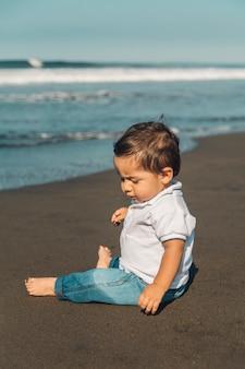 Piccolo neonato che si siede sulla sabbia della spiaggia