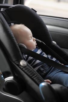 Piccolo neonato con gli occhi stretti nel seggiolino auto