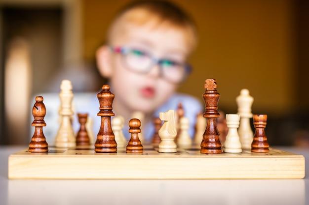 Piccolo neonato con sindrome di down con grandi occhiali blu che giocano a scacchi nella scuola materna