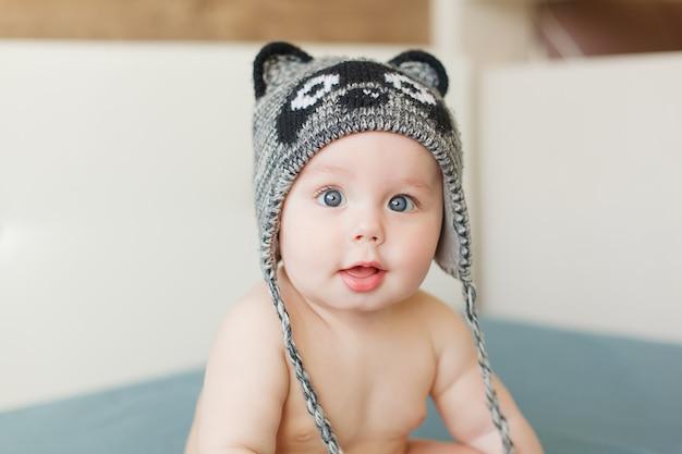 Piccolo neonato divertente con grandi occhi blu sorridente con cappuccio carino con le orecchie in testa