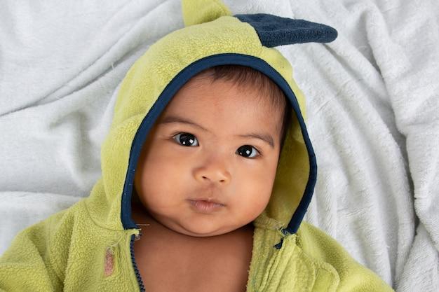 Piccolo neonato felice che si trova sulla coperta e sul sorriso molli