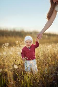 Piccolo neonato felice che sta e che sorride sulla natura nel giorno soleggiato di estate.