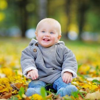 Piccolo neonato felice divertendosi nel parco di autunno