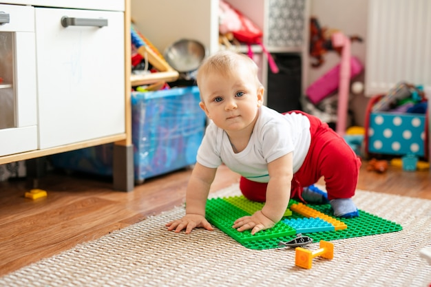 Piccolo neonato in maglietta bianca con giocattoli sul pavimento a casa