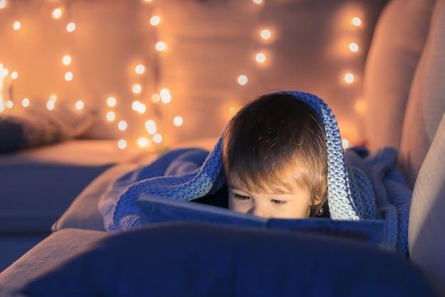 Piccolo neonato sveglio che legge un libro che si trova sul sofà