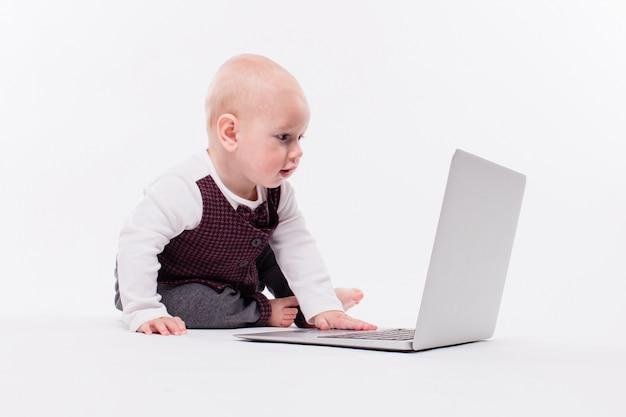 Piccolo neonato sveglio che si siede con il computer portatile