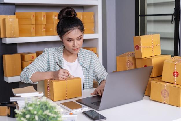 Piccolo proprietario di attività online, la donna che lavora con il computer portatile prepara le cassette dei pacchi per la consegna al cliente
