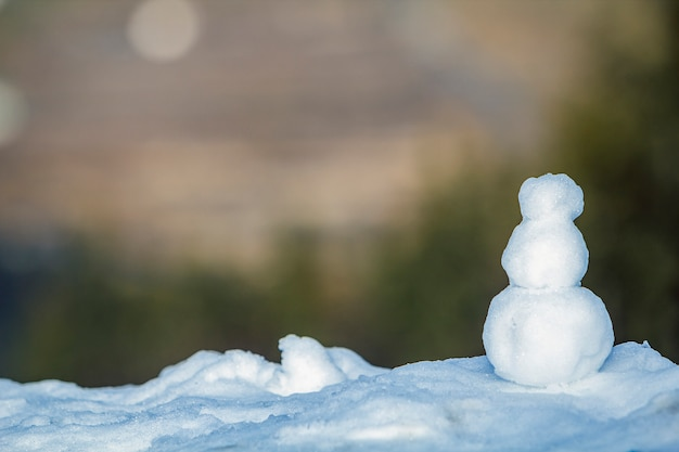 Piccolo pupazzo di neve bianco con sfondo verde sfocato in inverno