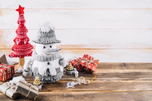 Piccolo pupazzo di neve con scatole regalo sul tavolo