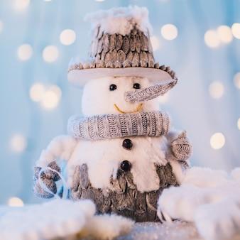 Piccolo pupazzo di neve giocattolo su sfondo sfocato