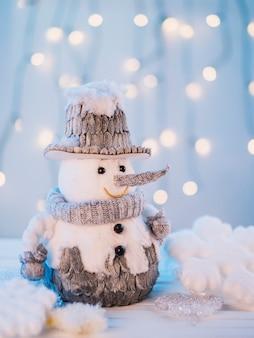 Piccolo pupazzo di neve giocattolo sul tavolo bianco
