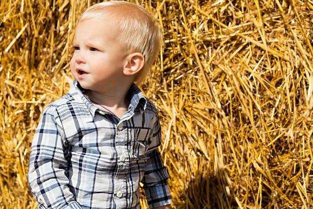 Piccolo ragazzo alla moda sullo sfondo di un pagliaio