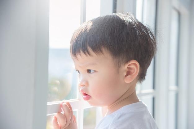 Piccolo ragazzo asiatico che guarda dalla finestra di mattina