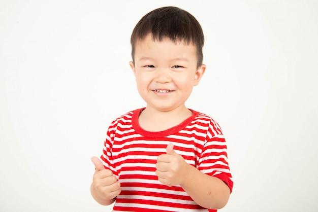 Piccolo ragazzo asiatico che mostra i pollici in su