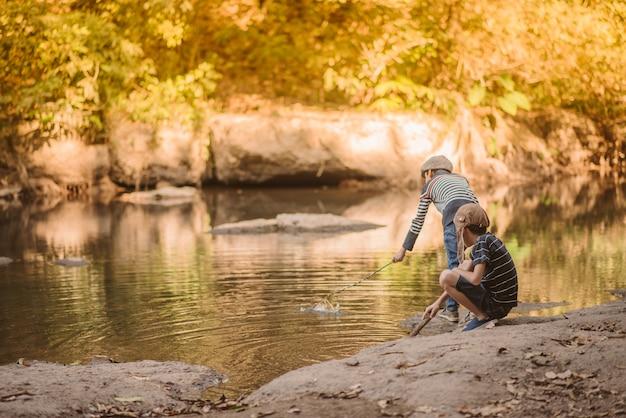 Piccolo ragazzo asiatico che pesca retro dell'annata del fiume