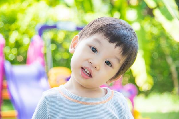 Piccolo ragazzo asiatico che sorride al campo da giuoco della scuola