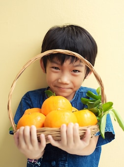 Piccolo ragazzo asiatico che tiene un cestino di grandi frutti di mandarini freschi
