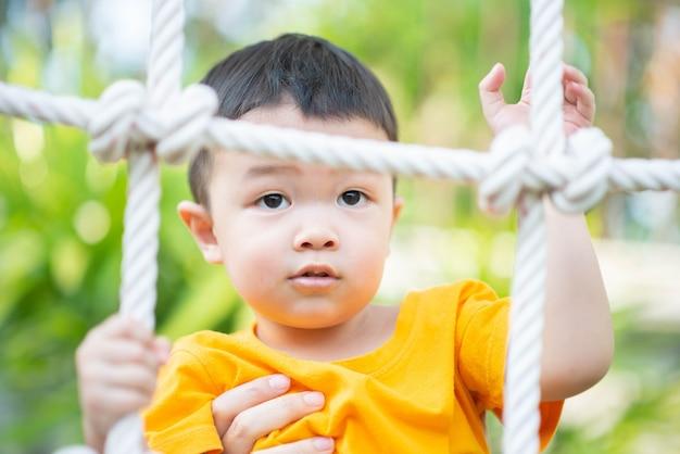 Piccolo ragazzo asiatico del bambino che si arrampica sulla corda al campo da giuoco