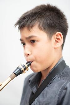 Piccolo ragazzo asiatico del musicista che gioca sassofono