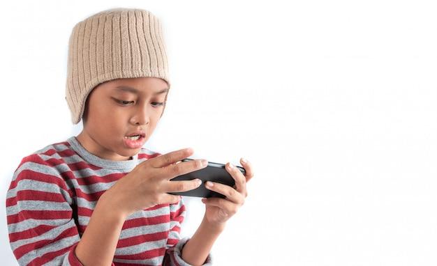 Piccolo ragazzo asiatico in cappello delle lane facendo uso dello smart phone su bianco
