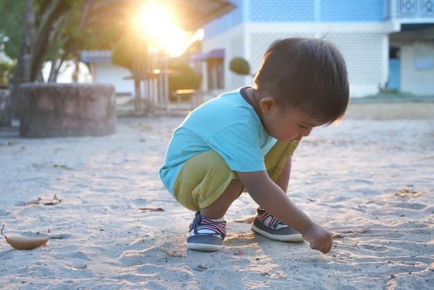 Piccolo ragazzo asiatico sveglio che gioca sabbia al parco