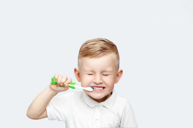 Piccolo ragazzo biondo che impara lavarsi i denti nel bagno domestico
