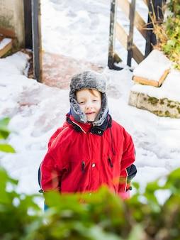 Piccolo ragazzo biondo in tuta sportiva di inverno all'aperto