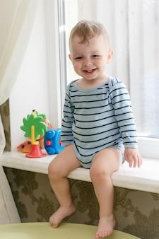 Piccolo ragazzo biondo sveglio che si siede sul davanzale della finestra