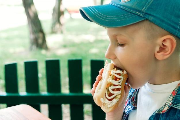 Piccolo ragazzo caucasico che mangia hamburger