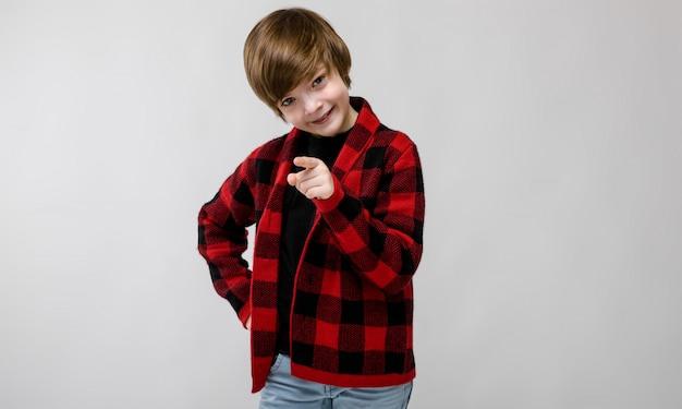 Piccolo ragazzo caucasico serio sicuro sveglio nell'indicare a quadretti della camicia