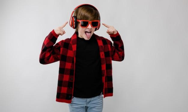 Piccolo ragazzo caucasico sicuro sveglio in camicia a quadretti in occhiali da sole che imbrogliano ascoltare la musica in cuffie su fondo grigio