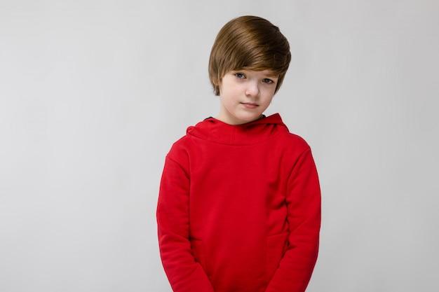 Piccolo ragazzo caucasico sicuro sveglio in maglione rosso su fondo grigio