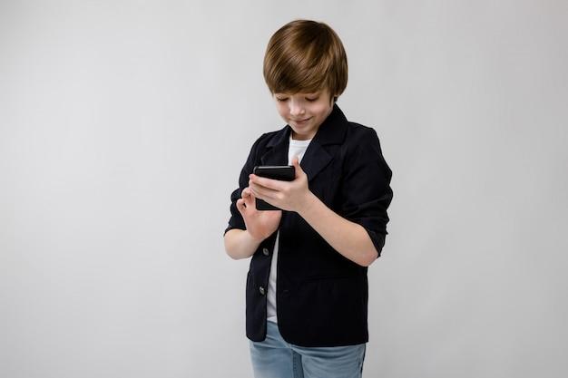 Piccolo ragazzo caucasico sicuro sveglio in rivestimento nero con il telefono cellulare