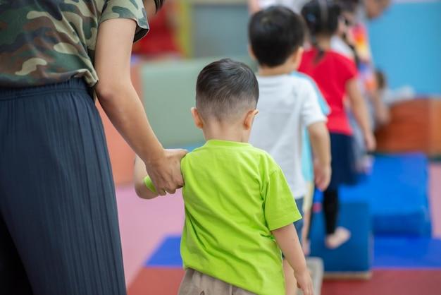 Piccolo ragazzo del bambino che risolve all'esercizio di ginnastica dell'interno