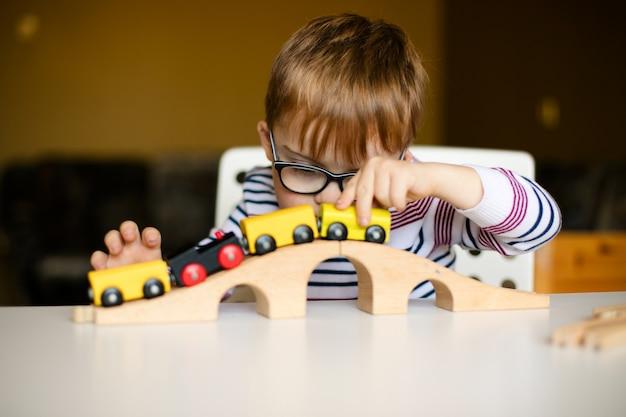 Piccolo ragazzo del bambino dello zenzero nei vetri con l'alba di sindrome che gioca con le ferrovie di legno