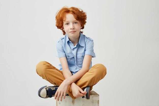 Piccolo ragazzo divertente con capelli arancio e le lentiggini che si siedono sulla scatola di legno