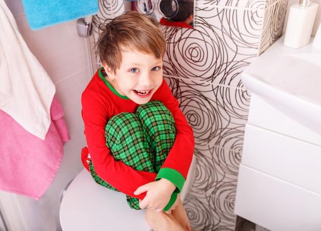 Piccolo ragazzo divertente con un'espressione divertente sul suo viso nel bagno