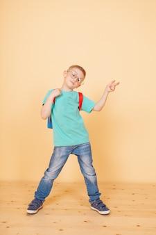 Piccolo ragazzo divertente in piedi con gli occhiali, zaino. sorprendente. isolato sul giallo.