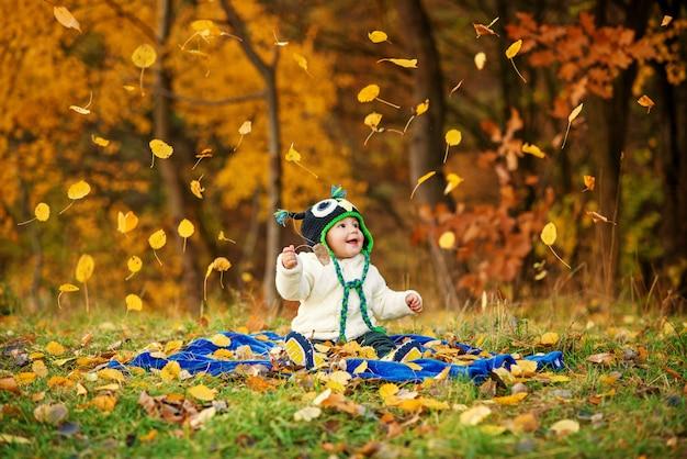 Piccolo ragazzo divertente in un cappuccio tricottato che si siede sull'erba con la zucca e alberi di autunno e foglie cadenti di autunno